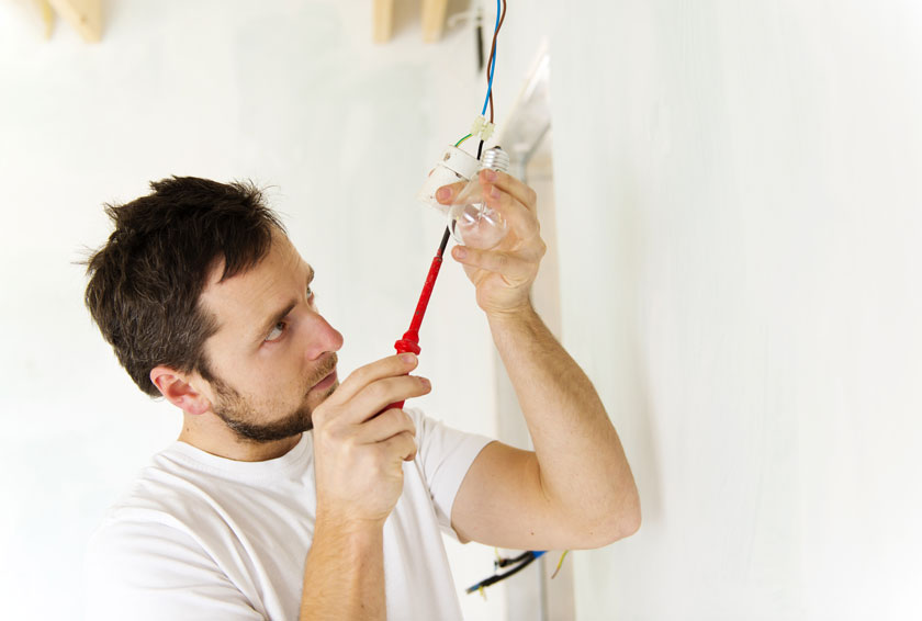 Man working on home project of fixing light
